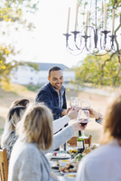 Friends toasting with wine at outdoor table 11018071544| 写真素材・ストックフォト・画像・イラスト素材|アマナイメージズ