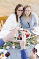 Caucasian man photographing friends at outdoor table 11018071553| 写真素材・ストックフォト・画像・イラスト素材|アマナイメージズ