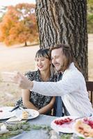 Couple taking selfie at outdoor table 11018071554| 写真素材・ストックフォト・画像・イラスト素材|アマナイメージズ