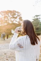 Caucasian woman drinking wine in rural field