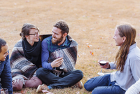 Friends drinking wine in rural field 11018071560| 写真素材・ストックフォト・画像・イラスト素材|アマナイメージズ