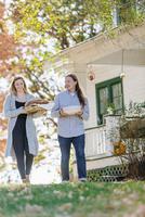 Caucasian couple carrying food in backyard 11018071561| 写真素材・ストックフォト・画像・イラスト素材|アマナイメージズ