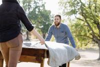 Caucasian couple spreading tablecloth on outdoor table 11018071565| 写真素材・ストックフォト・画像・イラスト素材|アマナイメージズ