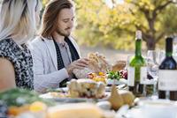 Couple eating at outdoor table 11018071566| 写真素材・ストックフォト・画像・イラスト素材|アマナイメージズ