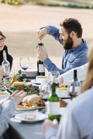 Man opening bottle of wine at outdoor table