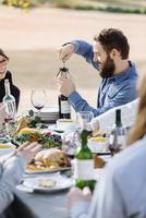 Man opening bottle of wine at outdoor table 11018071569| 写真素材・ストックフォト・画像・イラスト素材|アマナイメージズ