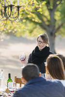 Woman toasting with wine at outdoor table 11018071573| 写真素材・ストックフォト・画像・イラスト素材|アマナイメージズ