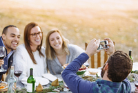Man photographing friends at outdoor table