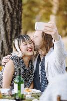 Couple taking selfie at outdoor table 11018071582| 写真素材・ストックフォト・画像・イラスト素材|アマナイメージズ
