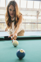 Hispanic woman playing pool