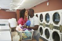 Kissing couple doing laundry at laundromat