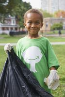 Boy picking up garbage in park