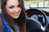 Hispanic woman smiling in car