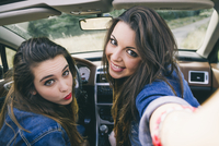 Women taking selfie in convertible