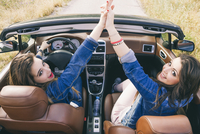Women high-fiving in convertible