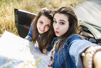 Women taking selfie with map on road trip