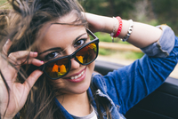 Hispanic woman peering over sunglasses