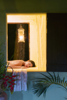 Hispanic woman laying on massage table in spa