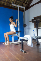Hispanic woman using exercise machine in gymnasium