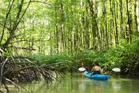 Hispanic woman rowing kayak on river 11018071640| 写真素材・ストックフォト・画像・イラスト素材|アマナイメージズ
