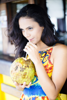 Hispanic woman drinking fresh coconut milk