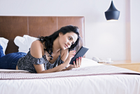 Hispanic woman using digital tablet on bed