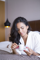 Hispanic woman drinking espresso on bed