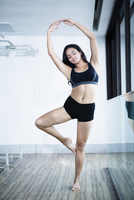 Hispanic woman practicing yoga in studio