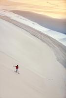 Man surfing on sand dunes on beach