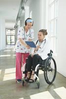 Caucasian nurse and paraplegic doctor talking in hospital 11018071668| 写真素材・ストックフォト・画像・イラスト素材|アマナイメージズ