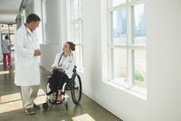 Caucasian paraplegic doctor and colleague talking in hospital 11018071669| 写真素材・ストックフォト・画像・イラスト素材|アマナイメージズ