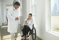 Caucasian paraplegic doctor and colleague talking in hospital 11018071670| 写真素材・ストックフォト・画像・イラスト素材|アマナイメージズ