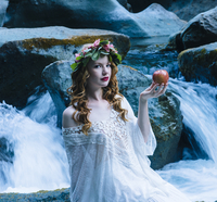 Caucasian woman holding apple at river waterfall