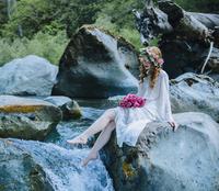 Caucasian woman wearing flower crown on rock at river waterfall