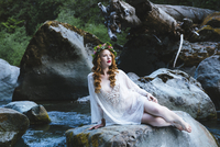 Caucasian woman wearing flower crown on rock at river