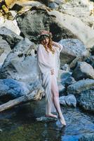 Caucasian woman wearing flower crown dipping toe in river