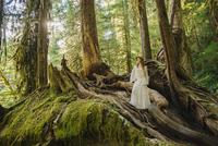 Caucasian woman standing on root in forest