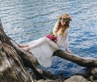 Caucasian woman wearing flower crown on log at river