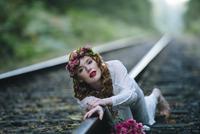 Caucasian woman laying on train tracks