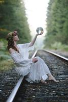 Caucasian woman holding crystal ball on train tracks