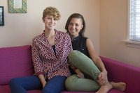 Caucasian lesbian couple smiling on sofa 11018071697| 写真素材・ストックフォト・画像・イラスト素材|アマナイメージズ