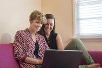 Caucasian lesbian couple using laptop on sofa 11018071699| 写真素材・ストックフォト・画像・イラスト素材|アマナイメージズ