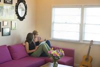 Caucasian lesbian couple reading book on sofa