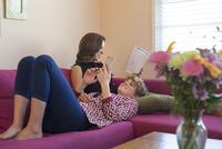 Caucasian lesbian couple using technology on sofa