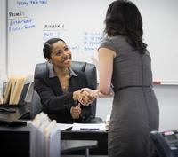 Businesswomen shaking hands in office 11018071710| 写真素材・ストックフォト・画像・イラスト素材|アマナイメージズ