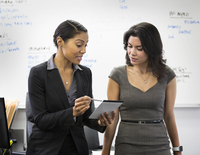 Businesswomen talking with notepad in office 11018071713| 写真素材・ストックフォト・画像・イラスト素材|アマナイメージズ