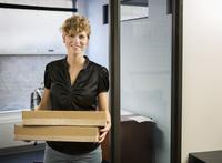 Caucasian businesswoman holding packages in office 11018071759| 写真素材・ストックフォト・画像・イラスト素材|アマナイメージズ