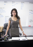 Mixed race businesswoman standing at desk in office