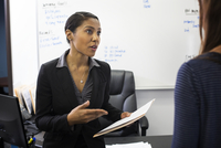 Businesswomen talking in office 11018071765| 写真素材・ストックフォト・画像・イラスト素材|アマナイメージズ