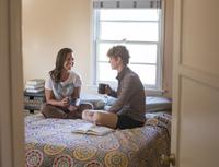 Caucasian lesbian couple sitting on bed 11018071769| 写真素材・ストックフォト・画像・イラスト素材|アマナイメージズ
